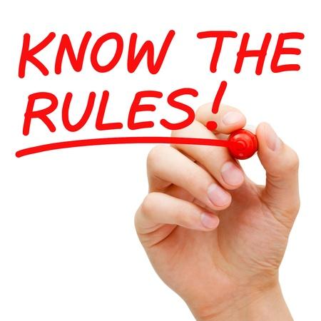 Hand writing connaître les règles avec marqueur rouge sur transparent essuyer bord.