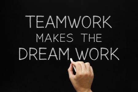 synergy: Escritura de la mano El trabajo en equipo hace el trabajo so�ado con tiza blanca sobre una pizarra. Foto de archivo