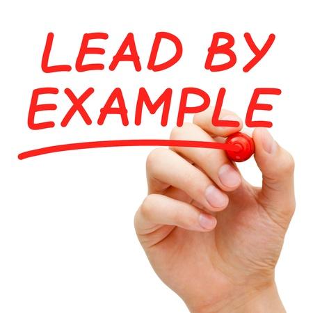 liderazgo: Mano escribiendo predicar con el ejemplo con marcador rojo sobre transparente limpiar bordo. Foto de archivo