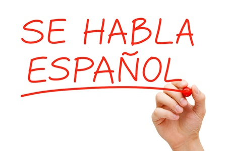 Hand writing Se Habla Espanol with red marker on transparent wipe board. Stock Photo
