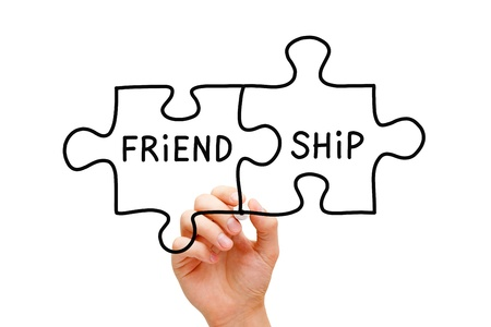 brotherhood: Hand drawing Friendship Puzzle Concept with black marker on transparent wipe board. Stock Photo