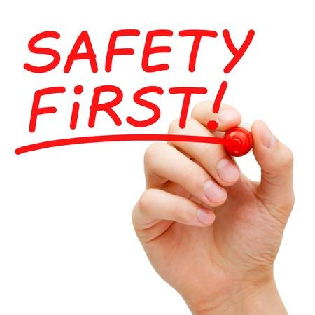 primeramente: Escritura de la mano seguridad es lo primero con marcador rojo en el tablero transparente toallita. Foto de archivo