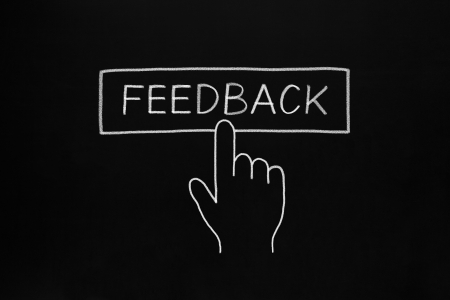 Hand clicking Feedback button drawn with white chalk on blackboard. Stock Photo - 19456174