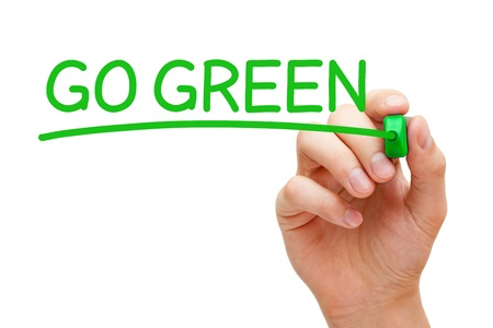 Hand writing Go Green with green marker on transparent wipe board. photo