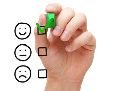Hand zetten vinkje met groene markering op klantenservice evaluatieformulier. Stockfoto