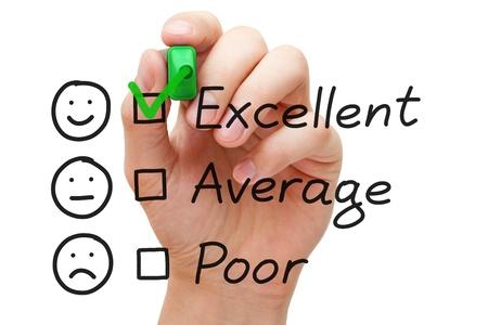Hand zetten vinkje met groene marker op een uitstekende klantenservice evaluatieformulier.