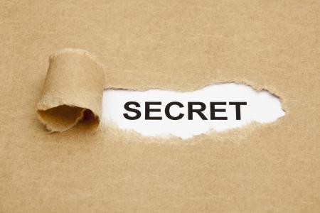 penetracion: La palabra secreta que aparece detr�s de papel marr�n rasgado. Foto de archivo