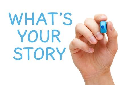 Mano escribiendo What's Your Story con marcador azul en tablero transparente.