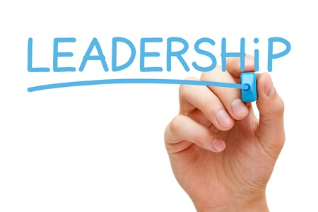 instructing: Hand writing Leadership with blue marker on transparent wipe board.