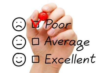 貧困層の顧客サービスの評価フォームに赤いマーカーで目盛りを置く手。 写真素材