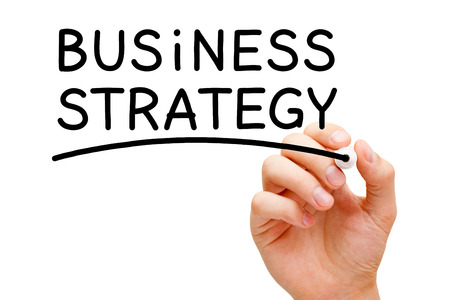 Hand writing Business Strategy with black marker on transparent wipe board. photo