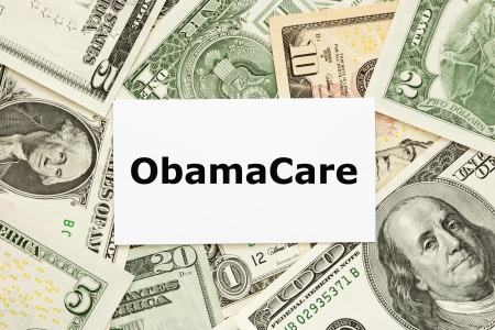medicare: ObamaCare printed on white card with US bills as a background. Stock Photo