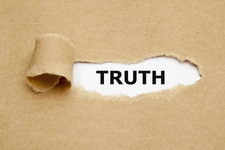 falso: La palabra verdad aparece detr�s de papel marr�n rasgado. Foto de archivo