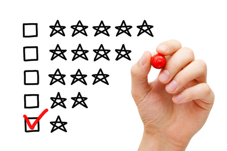 Hand putting check mark with red marker on poor one star rating. Stock Photo