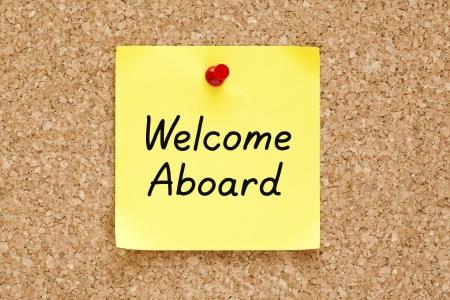 aboard: Welcome Aboard written on an yellow sticky note pinned on a cork bulletin board.