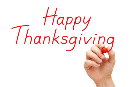 Hand writing Happy Thanksgiving with red marker on transparent wipe board. photo