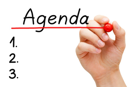 programs: Hand underlining Agenda with red marker on transparent wipe board. Stock Photo