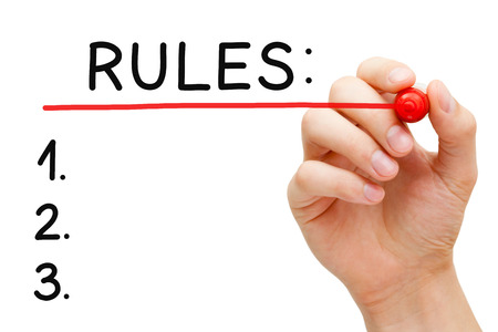 regulations: Hand underlining Rules with red marker on transparent wipe board.