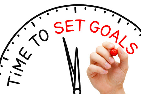 accomplishing: Hand writing Time to Set Goals concept with red marker on transparent wipe board.