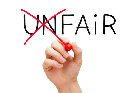 equitable: Hand changing the word Unfair into Fair with red marker isolated on white. Stock Photo
