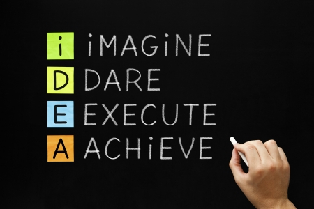 Hand writing IDEA - Imagine Dare Execute Achieve with white chalk on blackboard.