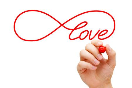 romance: Schizzi a mano il simbolo dell'Infinito Amore con un pennarello rosso sulla Lavagna trasparente. Concetto di trovare l'amore infinito.