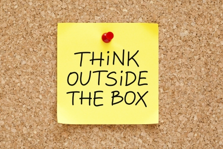 think out of the box: Think Outside The Box written on an yellow sticky note pinned on a cork bulletin board.