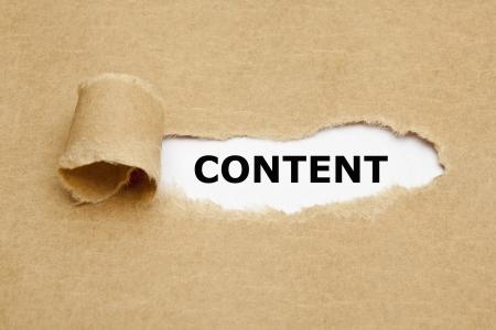 La palabra de contenido que aparece detrás de papel marrón rasgado. Foto de archivo