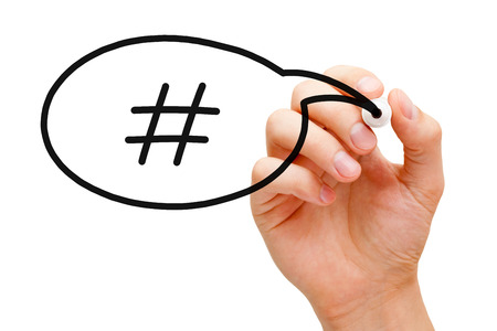 trending: Hand sketching Hashtag Speech Bubble Concept with black marker on transparent wipe board. Stock Photo