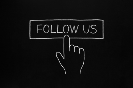 Hand clicking Follow Us button drawn with white chalk on blackboard. photo