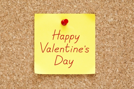 Happy Valentines Day written on an yellow sticky note pinned on a cork bulletin board. photo
