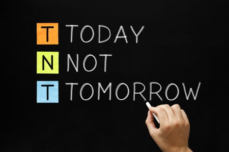 tomorrow: Hand writing Today Not Tomorrow with white chalk on blackboard.