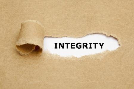 concept: La parola Integrity che appare dietro la carta marrone strappata. Archivio Fotografico