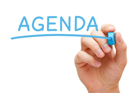 proactive: Hand writing Agenda with blue marker on transparent wipe board.