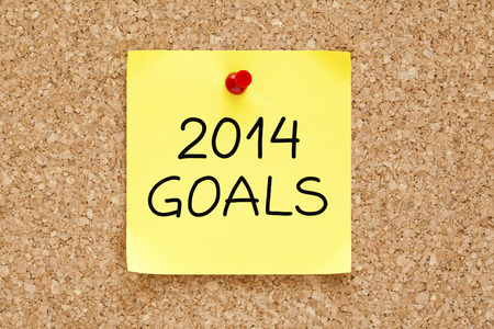 2014 Goals on yellow sticky note pinned with red push pin on cork board. photo