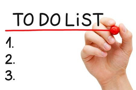 elenchi: Sottolineando mano per fare lista con pennarello rosso isolato su bianco. Archivio Fotografico