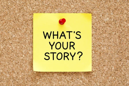 telling: Whats Your Story, written on an yellow sticky note pinned on a cork bulletin board. Stock Photo
