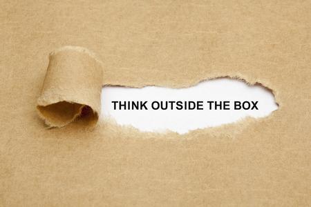 receptivo: Piense fuera de la caja que aparece detr�s de papel marr�n rasgado. Foto de archivo