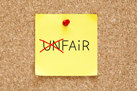 equitable: Turning the word Unfair into Fair with red marker on yellow sticky note pinned with red push pin.