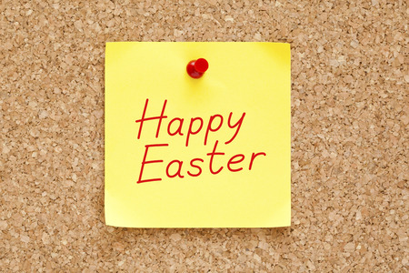 Happy Easter written on an yellow sticky note pinned on cork bulletin board. photo