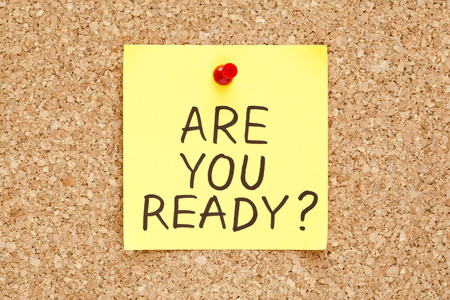 Are You Ready, written on an yellow sticky note on a cork bulletin board photo