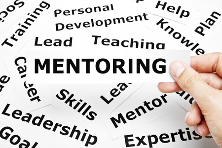 supervise: Hand holding a piece of paper with the word Mentoring on it