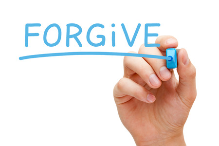 Hand writing Forgive with blue marker on transparent wipe board. photo