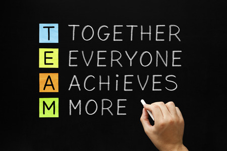achieves: Hand writing TEAM - Together Everyone Achieves More with white chalk on blackboard. Stock Photo