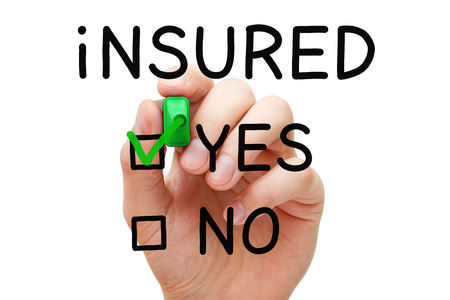 marker: Hand putting check mark with green marker on Yes Insured. Stock Photo