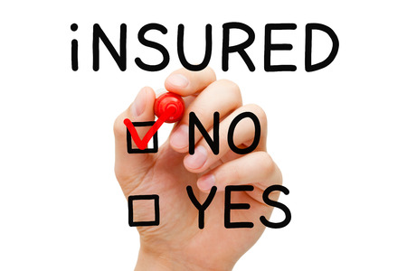 Hand putting check mark with red marker on No Insured. Standard-Bild