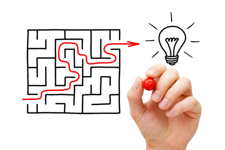 Hand drawing an red arrow going through a maze to a glowing light bulb. It's hard to find a great idea. Standard-Bild