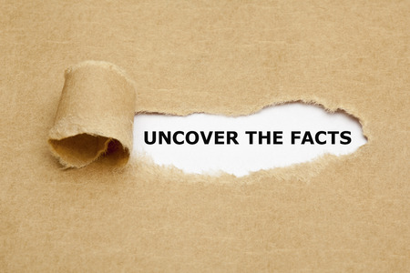 Uncover The Facts appearing behind torn brown paper.  photo
