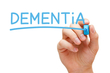 Hand writing Dementia with blue marker on transparent wipe board.