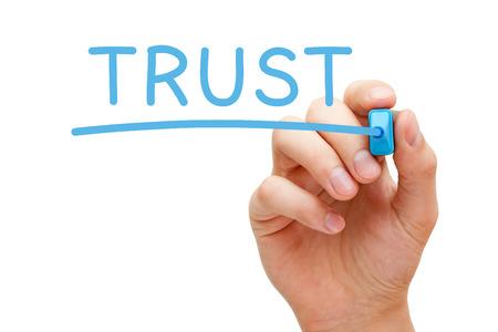 Hand schrijven Trust met blauwe marker op transparante veeg boord.